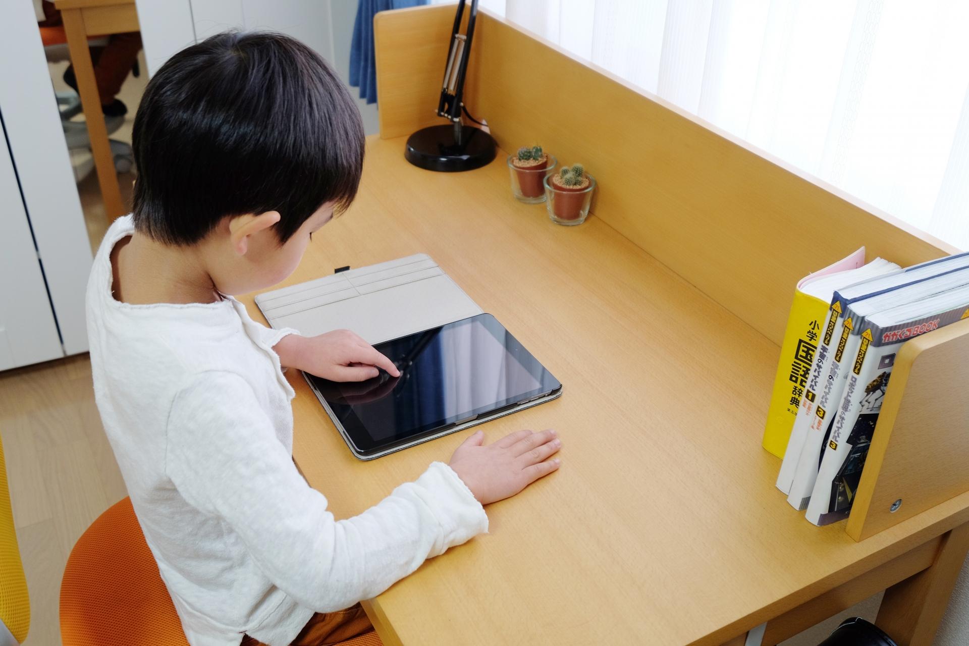 机でタブレットをさわる子ども