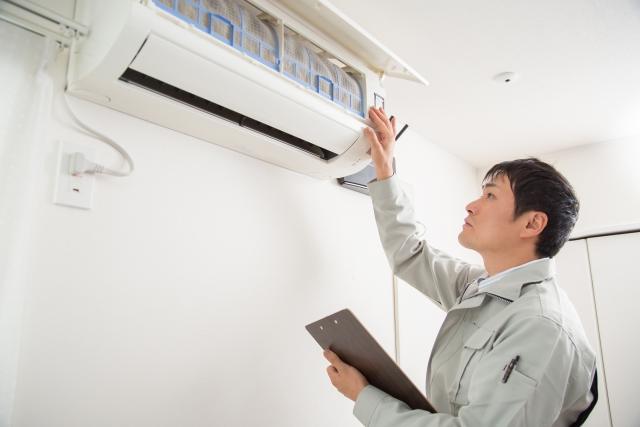 家庭用エアコンをチェックする作業員