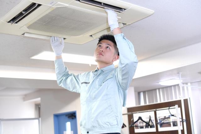 天井埋め込み式のエアコンをチェックする作業員