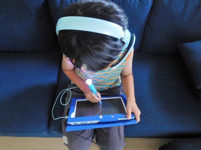 ソファでタブレット学習する少年