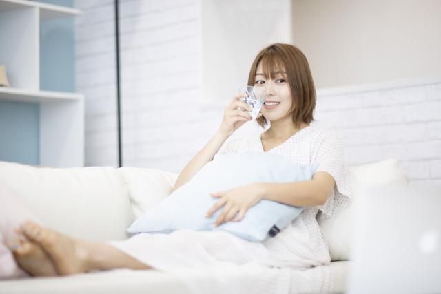 ソファに座って水を飲む女性
