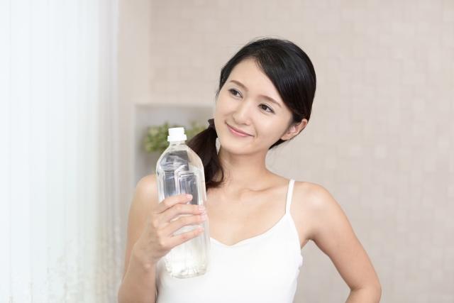 ペットボトルを持つ女性